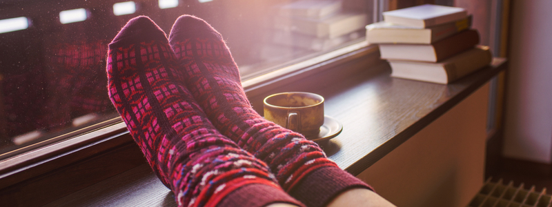 Feet up on window sill wearing comfy, cosy socks alongside a hot drink and some books