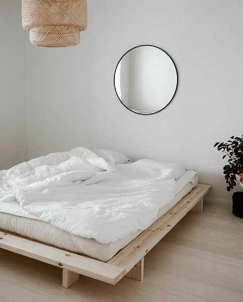 simple white bedroom with low wooden bed and white bed linen