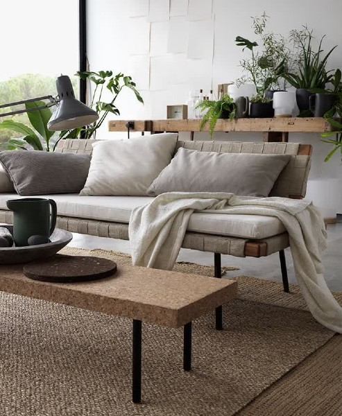 living room with house plants, simple sofa and natural-coloured rugs and throws and cushions